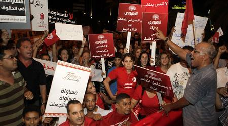 Protesters wave flags and shout slogans during a demonstration in Tunis August 13, 2012. Thousands of Tunisians rallied on Monday to protest against what they see as a push by the Islamist-led government for constitutional changes that would degrade women's status in one of the Arab world's most liberal nations. REUTERS-Zoubeir Souissi