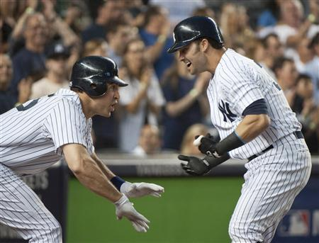New York Yankees batter Nick Swisher celebrates with teammate Mark Teixeira (L) after hitting a grand slam home run against the Texas Rangers in the third inning of their MLB American League game at Yankee Stadium in New York, August 13, 2012. REUTERS/Ray Stubblebine