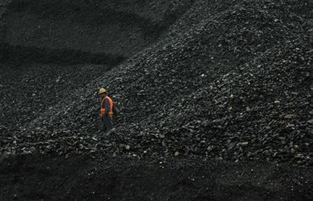 A labourer walks amid piles of coal at an opencast coal mine in Fuxin, Liaoning province May 30, 2012. REUTERS/Stringer