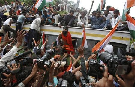 Baba Ramdev (C) leans out of a bus window after he was detained by police along with his supporters during a protest march against corruption in New Delhi August 13, 2012. REUTERS/Adnan Abidi