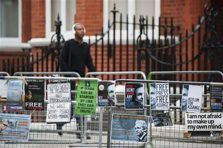 A man walks past a barrier with Free Julian Assange posters opposite the Ecuadorean Embassy in London August 14, 2012. REUTERS/Ki Price