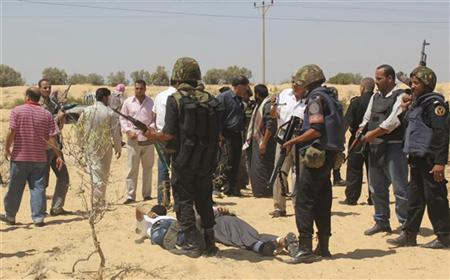 Egyptian security forces arrest suspected militants after a firefight at the al-Goura settlement in Egypt's north Sinai region, about 15 km (10 miles) from the border with Israel, August 12, 2012. REUTERS/Stringer