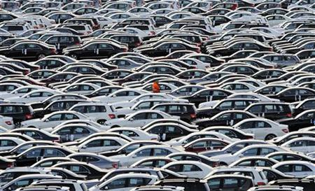 A worker walks along rolls of Mercedes cars at a shipping terminal in the harbor of the German northern town of Bremerhaven, March 8, 2012. REUTERS/Fabian Bimmer