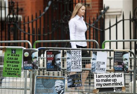 A women walks past a barrier with Free Julian Assange posters opposite the Ecuadorian Embassy in London August 14, 2012. REUTERS/Ki Price