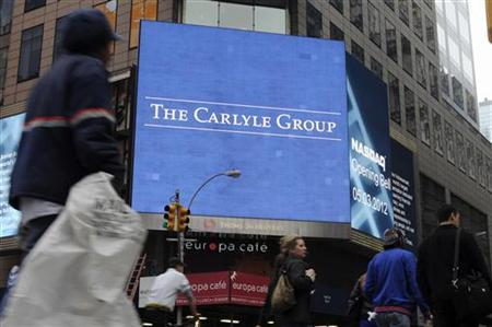 Passersby walk in front of video monitors announcing the Carlyle Group's listing on the NASDAQ market site in New York's Times Square after the opening bell for trading, May 3, 2012. REUTERS/Keith Bedford/Files
