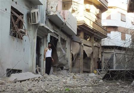 Syrian residents inspect houses destroyed by what they said was heavy shelling from Syrian President Bashar al-Assad forces in Banisaba'i area in Homs August 14, 2012. REUTERS/Yazan Homsy