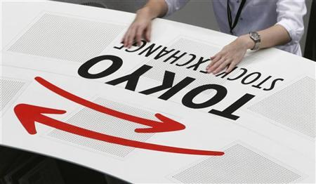 A Tokyo Stock Exchange employee rests his hands on a logo of the bourse in Tokyo June 4, 2012. REUTERS/Yuriko Nakao