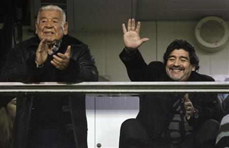 Argentine soccer legend Diego Maradona, coach of UAE's Al Wasl, waves next to his father, Diego Maradona Snr, as they wait for the start of the Argentine First Division soccer match between Boca Juniors and Arsenal in Buenos Aires June 17, 2012. REUTERS/Marcos Brindicci