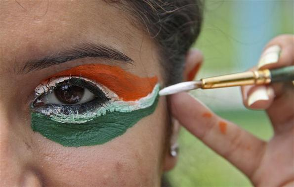 A college girl gets her eye painted in tri-colours of India's national flag on the eve of the country's Independence Day celebrations in Chandigarh August 14, 2012. REUTERS/Ajay Verma