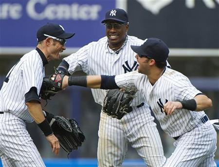 New York Yankees right fielder Ichiro Suzuki (L-R), center fielder Curtis Granderson and right fielder Nick Swisher celebrate after beating the Seattle Mariners in their MLB American League game at Yankee Stadium in New York, August 5, 2012. REUTERS/Ray Stubblebine