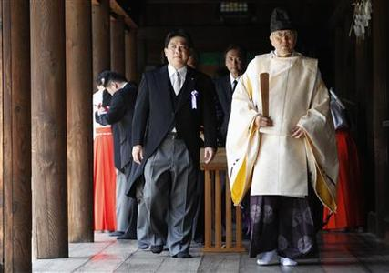 Japan's Land, Infrastructure, Transport and Tourism Minister Yuichiro Hata (C) and other lawmakers are led by a Shinto priest after offering prayers to war dead at Yasukuni Shrine in Tokyo August 15, 2012, on the 67th anniversary of Japan's surrender in World War II. REUTERS/Issei Kato