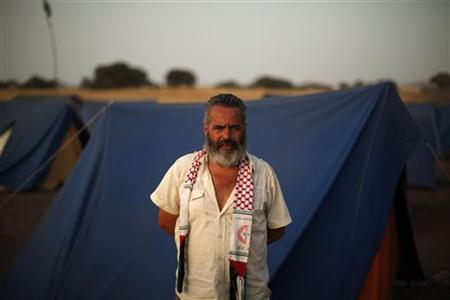 Marinaleda's Mayor and Izquierda Unida (IU) Parliamentarian Juan Manuel Sanchez Gordillo poses for a photograph next to tents at the Turquillas land in Osuna, southern Spain, late August 9, 2012. REUTERS-Jon Nazca