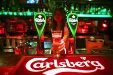 Бармен протягивает бокал пива Carlsberg в баре в Куала-Лумпур, 4 июля 2012 года. Датская пивоваренная компания Carlsberg получила во втором квартале меньшую, чем ожидал рынок, операционную прибыль, но сохранила прогноз на полный год за счет улучшения положения на ключевом для нее российском рынке. REUTERS/David Loh