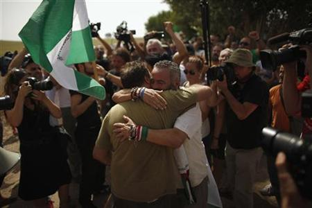 Marinaleda's Mayor and Izquierda Unida (IU) Parliamentarian Juan Manuel Sanchez Gordillo (R) embraces to a member of SAT (Andalusian Union of Workers), Andres Amaro, 43, as he arrives with Francisco Molero (not pictured) after they were released from a court in Ecija, at the Turquillas land, in Osuna, southern Spain, August 9, 2012. REUTERS-Jon Nazca