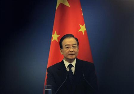 China's Premier Wen Jiabao stands in front of a Chinese national flag as he attends a joint news conference of the fifth trilateral summit among China, South Korea and Japan at the Great Hall of the People in Beijing, May 13, 2012. REUTERS/Petar Kujundzic