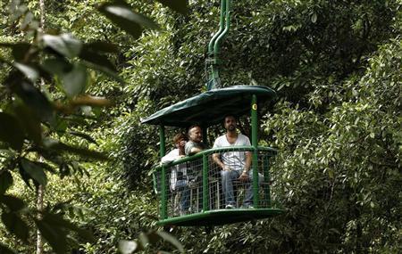Tourists take an aerial tram ride in the rainforest tram at the Braullio Carrillo National Park, 50 kilometers (31 miles) east of San Jose, June 5, 2012. REUTERS/Juan Carlos Ulate