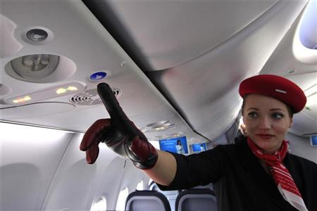 An airberlin stewardess shows the new call button in the Boeing 737 during 49th Paris Air Show at the Le Bourget Airport, near Paris June 21, 2011. REUTERS/Pascal Rossignol