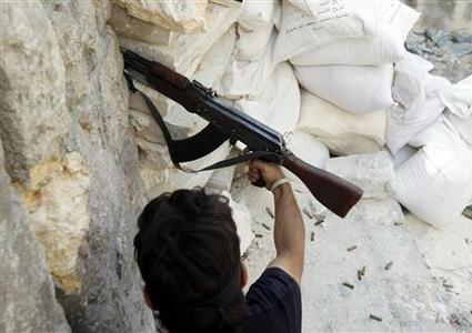 A Free Syrian Army fighter fires an AK-47 rifle in Aleppo August 15, 2012. REUTERS-Goran Tomasevic