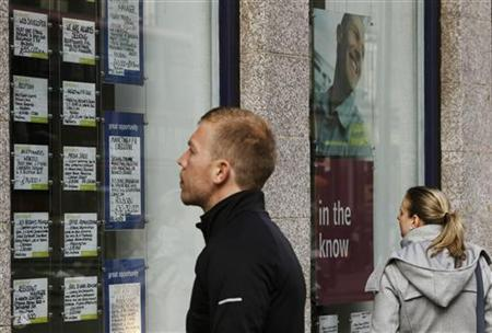 People look at adverts posted in the window of a recruitment agency in London March 14, 2012. REUTERS/Luke MacGregor