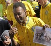"""Pelé segura uma fotografia do time brasileiro vitorioso de 1958 fazendo uma volta no estádio de Rasunda com a bandeira da Suécia, onde derrotaram os anfitriões por 5 a 2, vencendo a Copa do Mundo pela primeira vez. """"Eu me lembro de tudo"""", disse Pelé a jornalistas de volta ao palco da sua primeira grande conquista com a seleção. 14/08/2012 REUTERS/Phil O'Connor"""