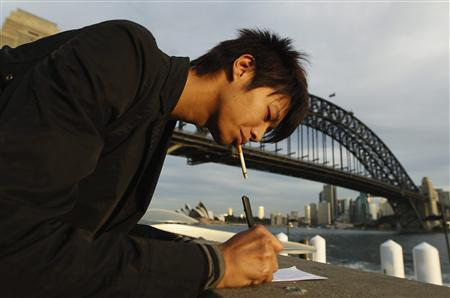 An office worker smokes a cigarette as he takes notes in front of the Sydney Harbour Bridge August 15, 2012. REUTERS/Daniel Munoz