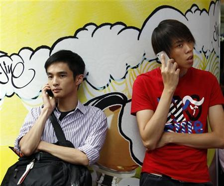 Two men use mobile phones as they wait outside a department store in Hong Kong August 16, 2011. REUTERS/Bobby Yip/Files