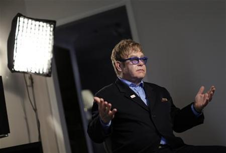 Musician Elton John gestures during an interview in Washington July 23, 2012. John was in town to speak at the AIDS 2012 conference. REUTERS/Kevin Lamarque/Files