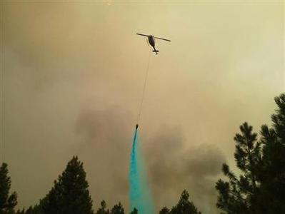 A helicopter drops Thermo-Gel on the Barry Point wildfire near Lakeview, Oregon, in this USDA Forest Service handout photo dated August 14, 2012. REUTERS/Lucinda Nolan/Fremont-Winema National Forest/Handout