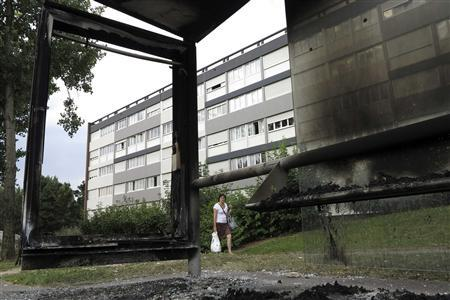 A local resident walks past a burnt bus stop in the north of Amiens August 15, 2012, a day after French riot police clashed with gangs of youths. REUTERS/Pascal Rossignol