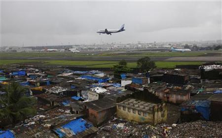 An aircraft prepares to land at the airport surrounded by slums in Mumbai July 20, 2010. REUTERS/Danish Siddiqui/Files