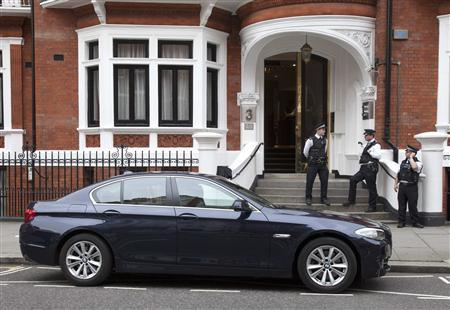 Police officers stand on the steps of Ecuador's embassy as an Ecuadorean diplomatic car is seen parked outside in London August 15, 2012. WikiLeaks founder Julian Assange has no way to leave the Ecuadorean embassy in London without getting arrested regardless of whether Ecuador grants him asylum or not, lawyers say. The Australian has been taking refuge at the embassy for eight weeks, since losing a legal battle to avoid extradition to Sweden where he is wanted to stand trial for rape. REUTERS/Neil Hall