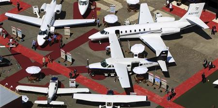 Visitors walk past aircrafts at the Latin American Business Aviation Conference and Exhibition (LABACE) fair at Congonhas Airport in Sao Paulo August 15, 2012. The fair runs from August 15 to 17. REUTERS/Paulo Whitaker