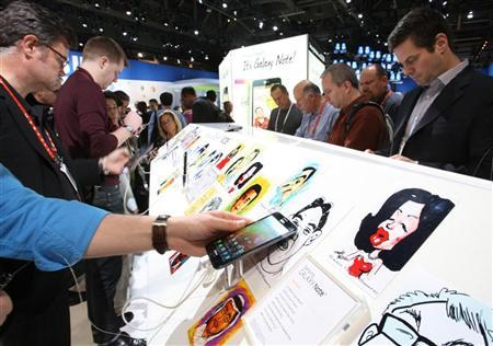 Showgoers look over the Samsung Galaxy Note phone/tablet during the 2012 International Consumer Electronics Show (CES) in Las Vegas, Nevada January 10, 2012. REUTERS/Steve Marcus