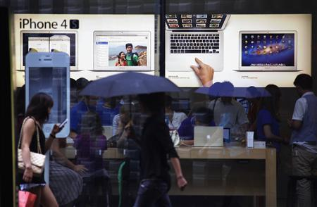 A woman uses an iPhone as she and other pedestrians walk past an Apple store in Beijing in this June 28, 2012 file photo. REUTERS/David Gray/Files