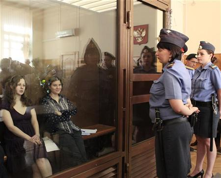 Yekaterina Samutsevich (2nd L) and Maria Alyokhina (L), members of female punk band ''Pussy Riot'', sit in the defendant's cell before a court hearing in Moscow August 8, 2012. REUTERS/Sergei Karpukhin