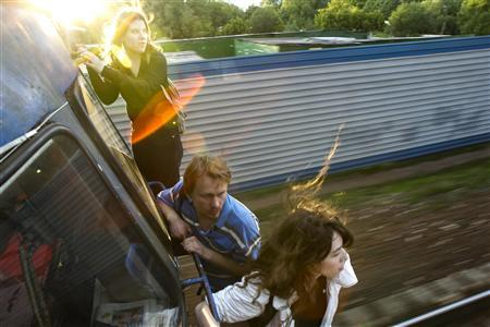 Yekaterina Samutsevich (R), Oleg Vorotnikov (C) and Natalia Sokol travel on the back of a commuter train after refusing to buy tickets outside of Moscow, June 2, 2008. REUTERS/Thomas Peter