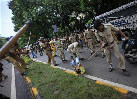 A demonstrator is beaten by policemen after a protest turned violent in Mumbai August 11, 2012. REUTERS/Danish Siddiqui