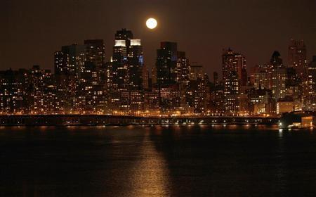 A full moon rises over the skyline of Manhattan along the Hudson River in New York, March 19, 2011. REUTERS/Gary Hershorn