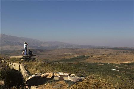 A man uses binoculars as he looks towards Syria from part of an abandoned military outpost near the Druze village of Buqata in the Golan Heights July 24, 2012. REUTERS/Ronen Zvulun