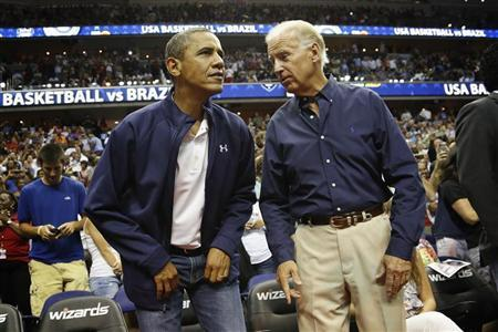 U.S. President Barack Obama (L) and Vice President Joe Biden take their seats for an Olympic basketball exhibition game between the U.S. and Brazil national men's teams in Washington, July 16, 2012. REUTERS/Jonathan Ernst