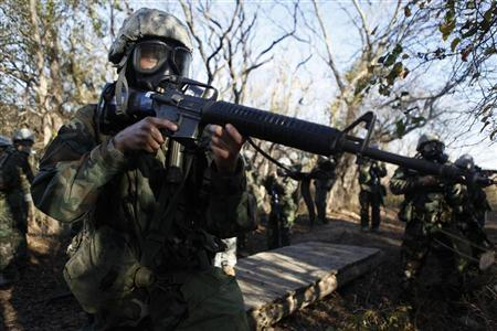 A U.S. Army recruit practices securing the area during a chemical weapons exercise at basic training at the Fort Sill Army Post in Fort Sill, Oklahoma November 5, 2009. REUTERS/Jessica Rinaldi