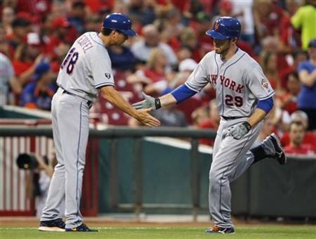 New York Mets third base coach Tim Teufel (18) congratulates Ike Davis (29) after hitting a solo home run off of Cincinnati Reds pitcher Homer Bailey during their MLB baseball game at Great American Ball Park in Cincinnati, Ohio, August 16, 2012. REUTERS/John Sommers II