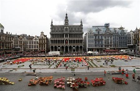 Gardeners design a giant flower carpet to form a floral decoration at Brussels' Grand Place August 14, 2012. The design requires about 700,000 flowers to create, according to event organisers. REUTERS/Francois Lenoir