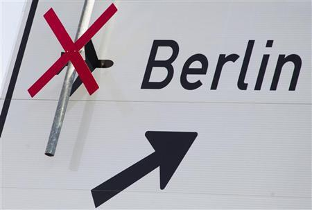 A cross strikes out the airport sign at the Berlin-Brandenburg airport motorway exit outside Berlin, August 15, 2012. REUTERS/Thomas Peter