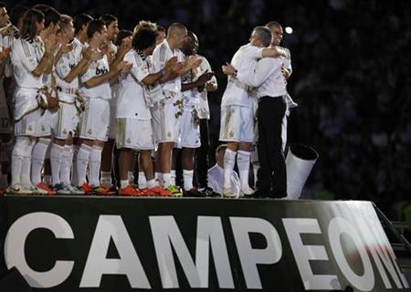 Real Madrid's coach Jose Mourinho embraces Cristiano Ronaldo as they celebrate their Spanish league first division 32nd title at Santiago Bernabeu stadium in Madrid, May 13, 2012. REUTERS/Paul Hanna/Files