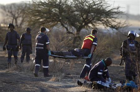 Paramedics carry an injured man after protesting miners were shot outside a South African mine in Rustenburg, 100 km (62 miles) northwest of Johannesburg, August 16, 2012. REUTERS-Siphiwe Sibeko