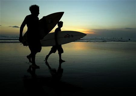 Two young surfers walk in from the surf at sunset on Legian beach near Kuta on the Indonesian resort island of Bali April 10, 2004. REUTERS/Darren Whiteside