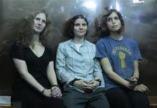 Integrantes da banda punk Pussy Riot (esq. para direita) Nadezhda Tolokonnikova, Yekaterina Samutsevich e Maria Alyokhina sentam-se em cela de vidro durante audiência em tribunal de Moscou. Juíza russa sentenciou as três mulheres da banda a dois anos de prisão. 17/08/2012 REUTERS/Maxim Shemetov