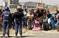 Policemen look on as women carrying placards chant slogans in protest against the killing of miners by South African police on Thursday, outside a South African mine in Rustenburg, 100 km (62 miles) northwest of Johannesburg, August 17, 2012. REUTERS/Siphiwe Sibeko