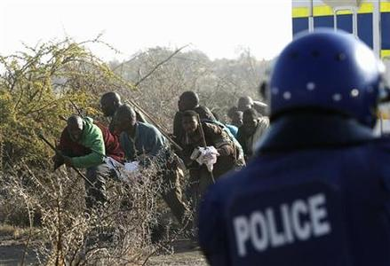 A policeman (R) fires at protesting miners outside a South African mine in Rustenburg, 100 km (62 miles) northwest of Johannesburg, August 16, 2012. REUTERS/Siphiwe Sibeko